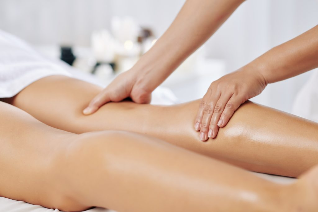 Hands of massage therapist massaging legs of young woman in spa salon